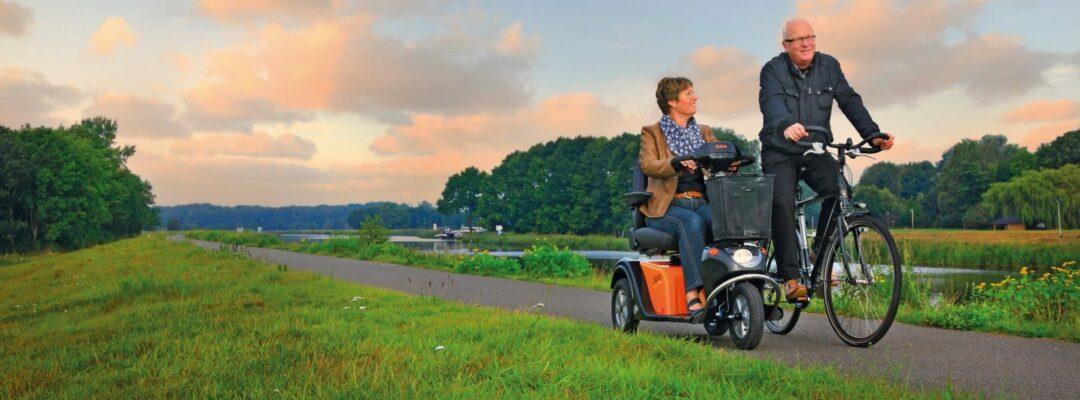 Vrouw op oranje scootmobiel over dijk | De Scootmobiel Winkel